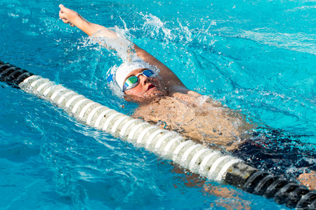 Photo pour Close up action shot of teen boy swimming backstroke in swimming pool. - image libre de droit