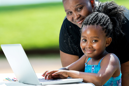 Photo for Close up portrait of little african girl with braids and mother with laptop.Kid typing on laptop against green background outdoors. - Royalty Free Image