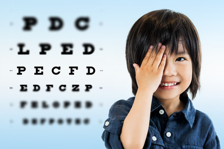 Photo pour Close up portrait of cute little asian boy doing eye test.Kid closing one eye with hand against alphabetical out of focus test chart in background. - image libre de droit