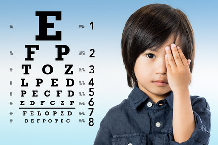 Photo pour Close up portrait of little Asian boy reviewing eyesight. Kid closing one eye with hand and  alphabetical eye test chart in background. - image libre de droit