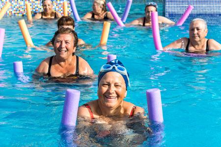Foto de Group of active senior women doing aqua gym in outdoor swimming pool. - Imagen libre de derechos