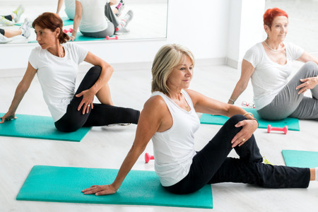Photo for Group of middle aged women warming up in gym.Threesome sitting on floor on rubber mattresses. - Royalty Free Image