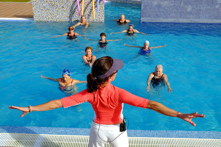 Close up rear view of fitness trainer at senior health class session in outdoor swimming pool.