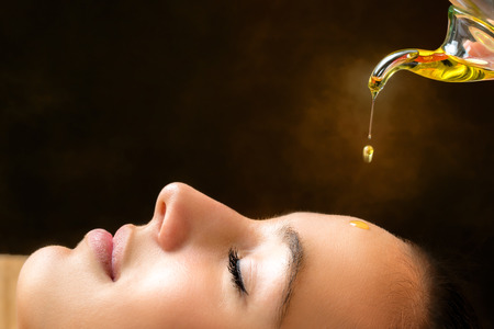 Foto de Macro close up portrait of young woman at ayurvedic massage session with aromatic oil dripping on face. - Imagen libre de derechos
