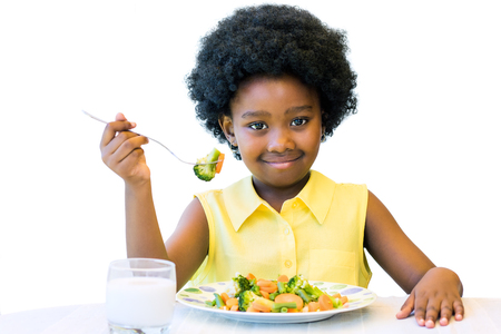 Photo pour Close up portrait of cute african girl with afro hairstyle eating healthy vegetable dish. Isolated on white. - image libre de droit