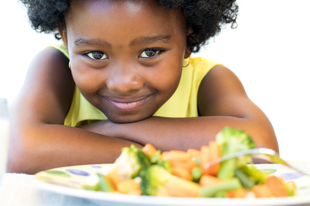 Photo pour Close up face shot of cute African girl in front of healthy vegetable dish. Isolated on white. - image libre de droit