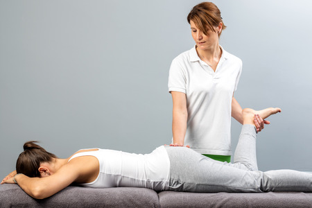 Close up of female physiotherapist doing manipulative leg therapy on patient.Therapist relieving sciatic nerve pain.