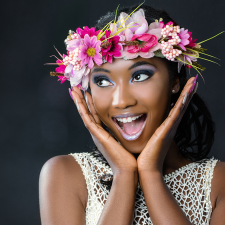 Foto de Close up fun portrait of attractive young african bride wearing colorful flower garland.Girl pulling funny face with hands next to face looking at corner. - Imagen libre de derechos