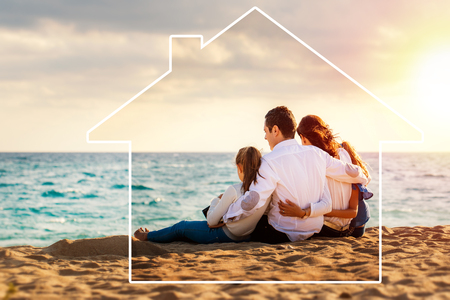 Photo pour Conceptual late afternoon outdoor portrait of young parents sitting on beach with kids.Foursome giving back against sea and cloud background. House icon drawing around family. - image libre de droit