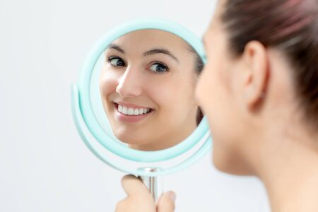 Foto de Close up portrait of young woman looking in mirror at herself. Girl with healthy white teeth holding hand mirror. - Imagen libre de derechos
