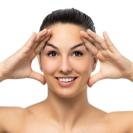 Photo pour Close up beauty portrait of attractive young woman stretching facial skin with hands.Girl with hands on both sides of face. Isolated on white background. - image libre de droit