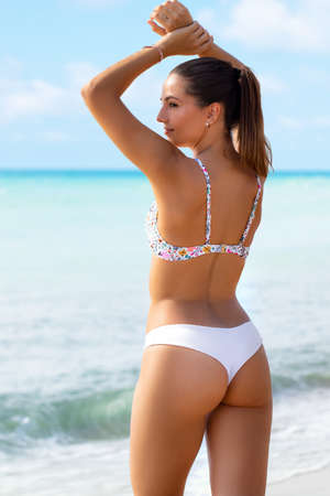 Foto de Close up rear view attractive young girl in bikini showing perfect buttock. Woman standing on beach against ocean background. - Imagen libre de derechos