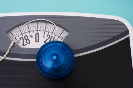 Blue yo-yo sitting on scales on blue background