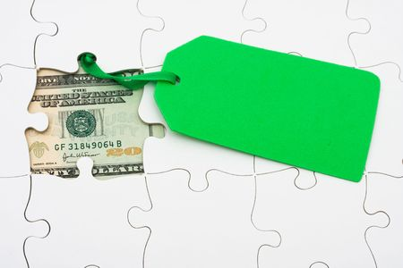 Puzzle with money under it and green sale tag. understanding finances