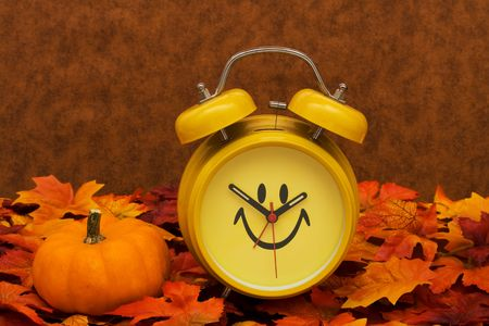 Photo pour Fall leaves with yellow clock and pumpkin on brown background, fall back time change - image libre de droit
