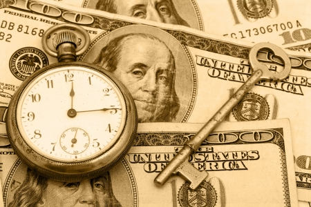 A pocket watch sitting with an antique key on a hundred dollar bill background, time management