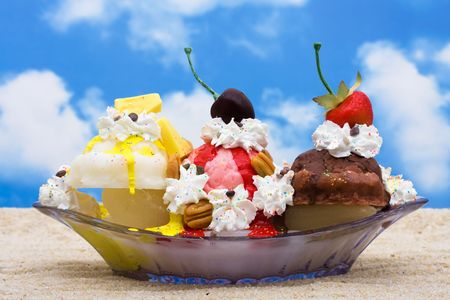 A banana split ice cream sitting on sand with a sky background