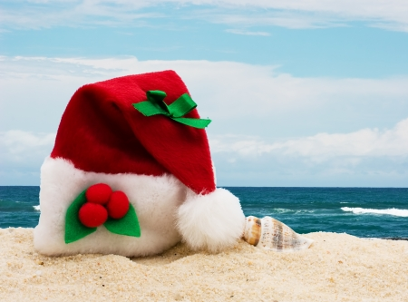 Photo for A Christmas hat the sand at the beach, Winter vacation getaway - Royalty Free Image