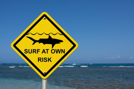 An warning sign at the beach with shark symbol and words surf at own risk, Use caution when surfing because sharks are present