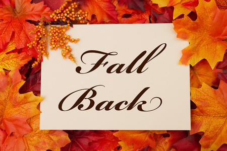 A Fall Back card, A beige card with words Fall Back over red and orange maple leaf background