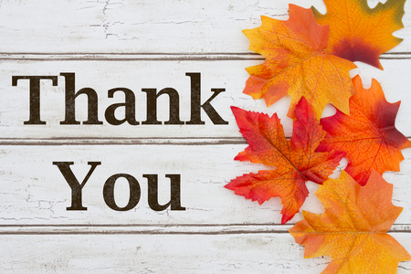 Thank You written on grunge wood background with Autumn Leaves