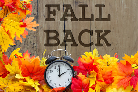 Fall Back Time Change, Autumn Leaves and Alarm Clock with grunge wood and words Fall Back
