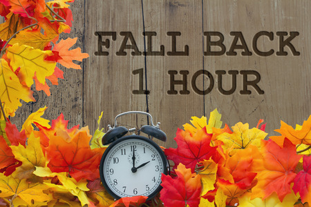 Fall Time Change, Autumn Leaves and Alarm Clock with grunge wood with text Fall Back 1 Hour
