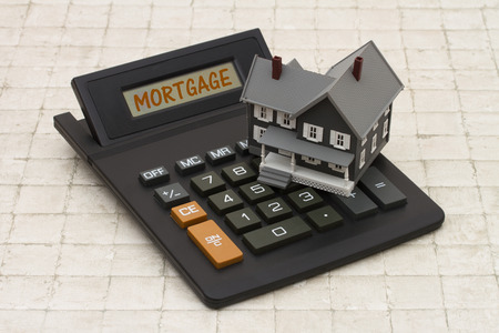 Photo pour Home Mortgage, A gray house and calculator on stone background with text Mortgage - image libre de droit
