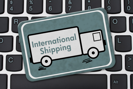 International Shipping Sign, A teal hanging sign with text International Shipping on a truck on a keyboard