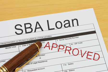 SBA Loan application form with a pen on a desk with an approved stamp