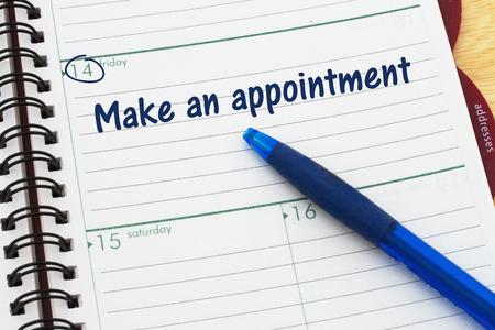 Photo pour A day planner with blue pen with text Make an appointment - image libre de droit