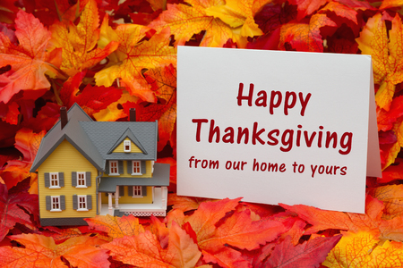 Photo for Some fall leaves and yellow and gray house and  greeting card with text Happy Thanksgiving from our home to yours - Royalty Free Image