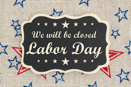 Photo pour We will be closed Labor Day text on a chalkboard with patriotic USA red and blue stars on burlap - image libre de droit
