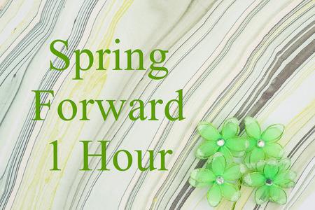 Photo pour Spring forward 1 hour DST message green flowers on textured watercolor paper - image libre de droit