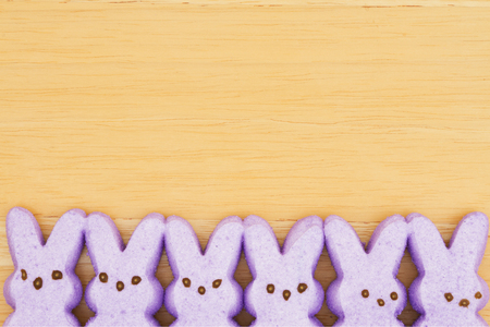 Photo for Purple candy bunnies on textured wood background with copy space for your Easter message - Royalty Free Image