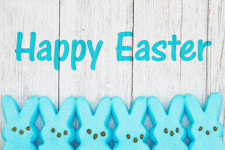 Photo for Happy Easter card with blue candy bunnies on weathered whitewash wood - Royalty Free Image
