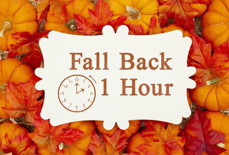 Foto de Fall Back 1 hour time change message on a metal sign on pumpkins and a straw hay - Imagen libre de derechos