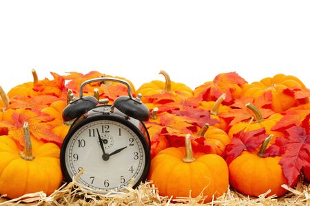 Photo pour Retro alarm clock with orange pumpkins with fall leaves on straw hay isolated over white with copy space for your message - image libre de droit