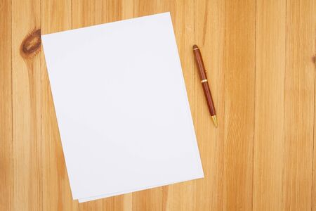 Photo for Pen and paper on pine wood desk with grain texture with copy space for your business or writing message - Royalty Free Image