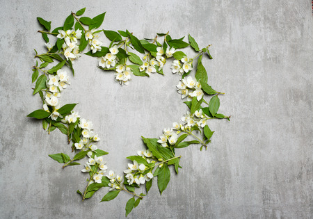 Beautiful white jasmine flowers formed as a heart on gray concrete background