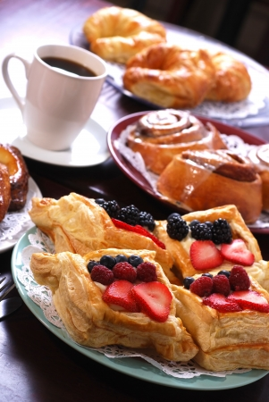 Plates full of assorted pastries with coffee in a bakery