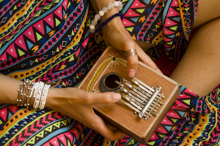 Photo pour Woman holding kalimba in her hands and playing - image libre de droit