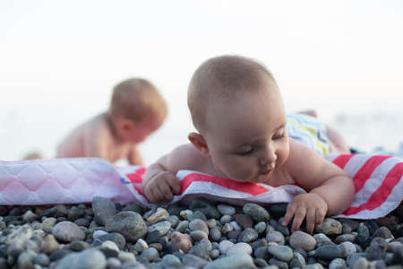Foto de Babies touching pebble on the beach. Exploring the world by playing. 2 kids are laying on striped red and white cover. - Imagen libre de derechos