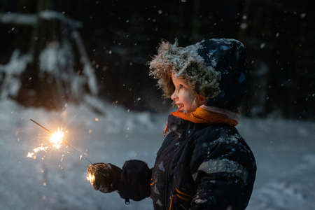 Photo pour Toddler girl in winter clothes walking outside and holding sparkler in her hand. It is dark and snowy, girl is happily smiling. Magic winter holidays mood - image libre de droit