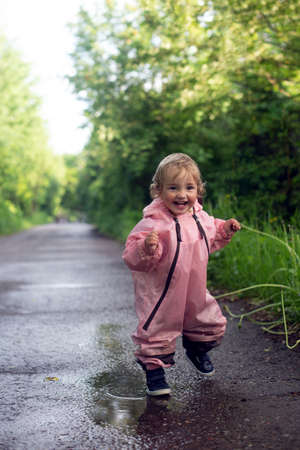 Photo pour Happy carefree toddler girl running throuh the puddles after rain in summer day. Vertical fromat. Baby is wearing pink waterproof overall - image libre de droit