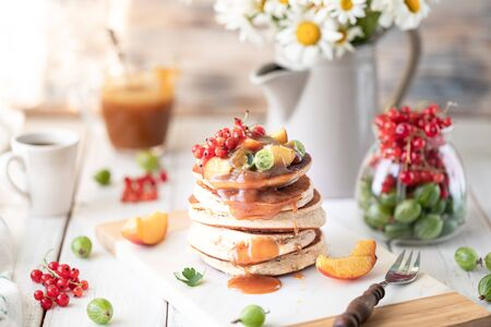 Photo pour Cornmeal pancakes with salted caramel served with berries and fruits on a white wooden background. Rustic - image libre de droit