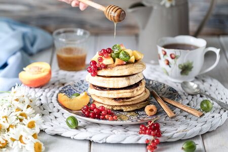 Photo for Cornmeal pancakes with honey, served with berries and fruits on a white wooden background. Rustic - Royalty Free Image