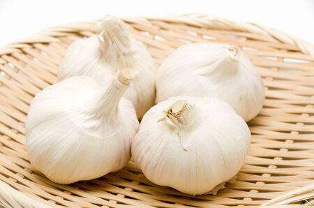 Foto für Fresh garlic in bamboo colander on white background - Lizenzfreies Bild