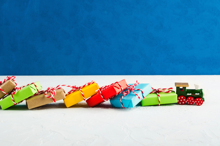 Foto de Train transports many colorful Christmas gifts in paper with blue background, copy space - Imagen libre de derechos