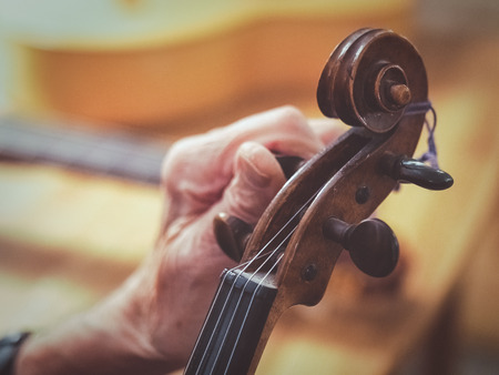 Photo for An old man luthier with aged hands is tuning a violin. You see other instruments like a guitar blurred in the background. - Royalty Free Image